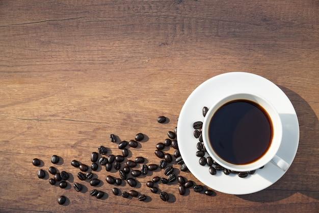 Weiße kaffeetasse und kaffeebohnen auf der hölzernen schreibtischtabelle.
