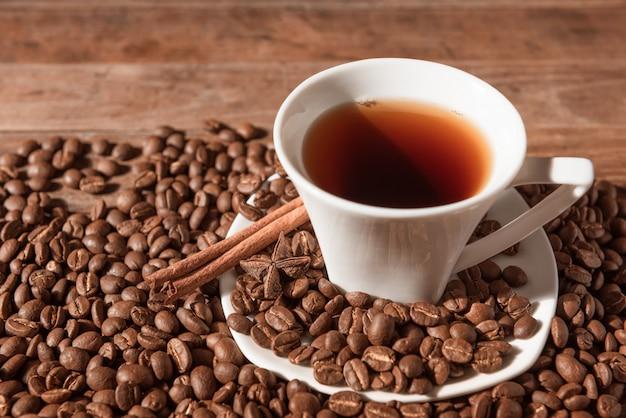 Weiße kaffeetasse und kaffeebohnen auf hölzerner tabelle