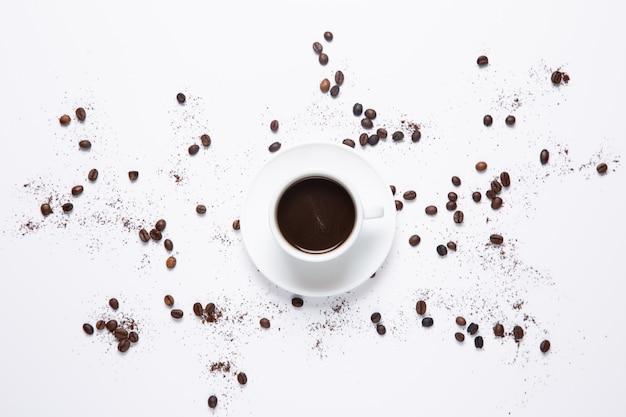 Weiße kaffeetasse und kaffeebohnen