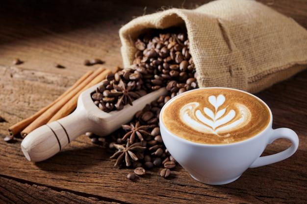 Weiße kaffeetasse und röstkaffeebohnen herum