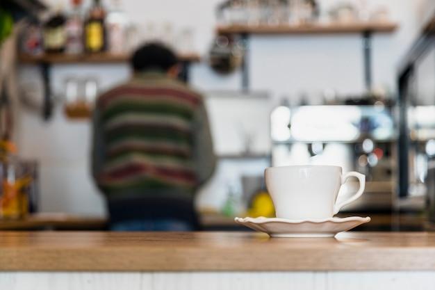 Weiße kaffeetasse und untertasse auf kaffeezähler