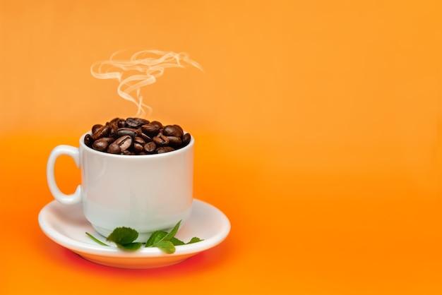 Weiße kaffeetasse voll von kaffeebohnen auf einem orangefarbenen hintergrund mit rauch an der spitze. das konzept des internationalen kaffeetages.