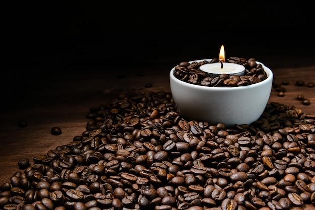 Weiße kaffeetasse voll von kaffeebohnen und brennender kerze oben auf kaffeebohnenstapel
