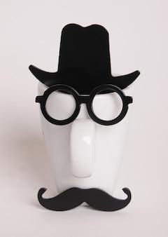 Weiße kaffeetasse wie ein mann auf weißem hintergrund. hipster-stil, brille, schnurrbart, hut