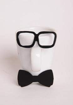 Weiße kaffeetasse wie ein mann auf weißem hintergrund. hipster-stil, fliege, brille