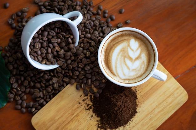 Weiße kaffeetassen und kaffeebohnen auf einen holztisch gegossen, wunderschön arrangiert,