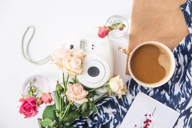 Weiße kamera auf dem desktop unter den blumen neben einer tasse kaffee. draufsicht flach liegend