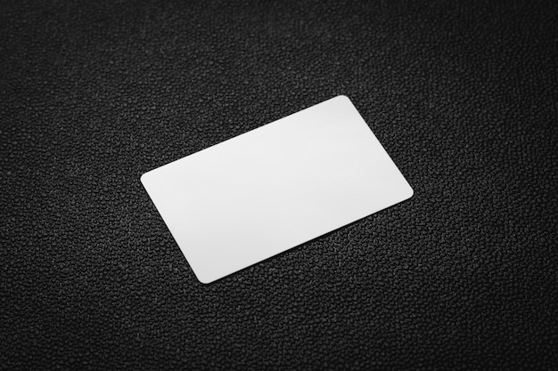 Weiße karte auf dunklem ledernem hintergrund. leere visitenkarte.