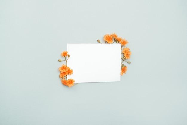 Weiße karte für glückwünsche und wünsche mit orange blumen herum.