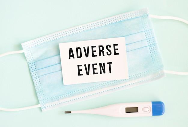 Weiße karte mit der aufschrift adverse event auf einer medizinischen schutzmaske. medizinisches konzept.