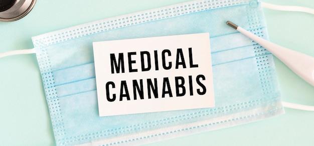 Weiße karte mit der aufschrift medical cannabis auf einer medizinischen schutzmaske