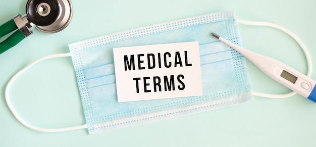 Weiße karte mit der aufschrift medical terms auf einer medizinischen schutzmaske. medizinisches konzept.