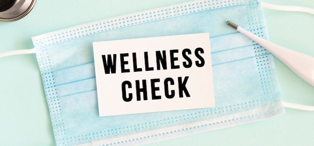 Weiße karte mit der aufschrift wellness check auf einer medizinischen schutzmaske. medizinisches konzept.