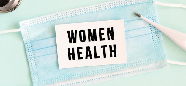 Weiße karte mit der aufschrift women health auf einer medizinischen schutzmaske.