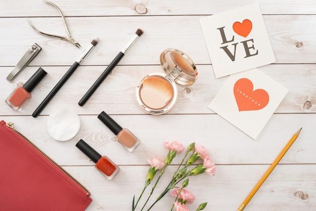 Weiße karte mit einem muster in form von herzen, maniküre-set und nagellack auf holzhintergrund. valentinstag. flach