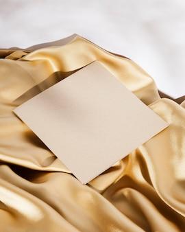 Weiße karte mit hohem winkel auf goldenem stoff