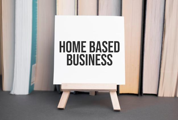 Weiße karte mit text home based business steht auf dem schreibtisch vor dem hintergrund gestapelter bücher