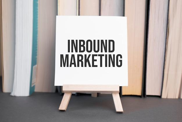 Weiße karte mit text-inbound-marketing steht auf dem schreibtisch vor dem hintergrund gestapelter bücher books