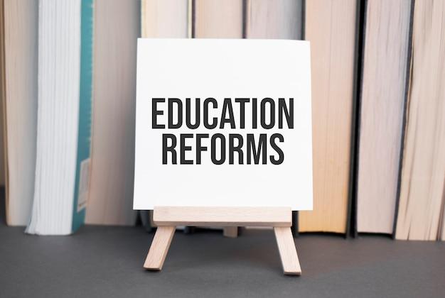 Weiße karte mit textbildungsreformen steht auf dem schreibtisch vor dem hintergrund gestapelter bücher