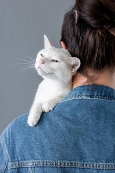 Weiße katze, die auf inhaberschulter sitzt