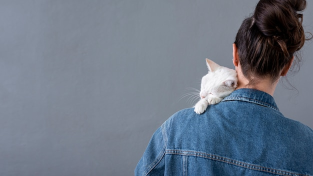 Weiße katze, die auf weiblicher schulter sitzt