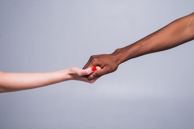 Weiße kaukasische weibliche hand und schwarze männliche hand, die finger zusammenhalten