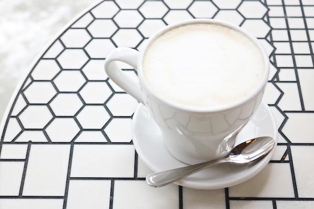 Weiße keramik-teetasse mit untertasse und edelstahl-teelöffel