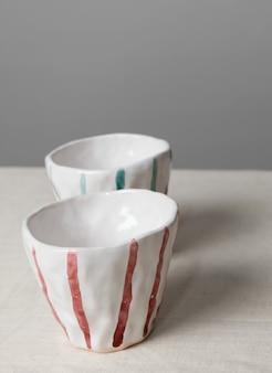 Weiße keramikbecher mit bunten streifen auf dem tisch mit leinentischdecke und grauem wandhintergrund. nahaufnahme handgemachte keramik, vertikal