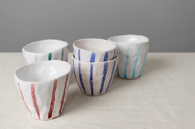 Weiße keramikbecher mit bunten streifen mit selektivem fokus auf tisch mit leinentischdecke und grauem wandhintergrund. handgefertigte keramik
