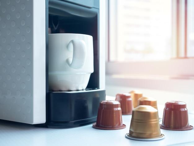 Weiße keramikkaffeetasse auf kaffeemaschine.