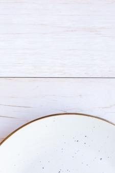 Weiße keramikplatte auf holzoberfläche, draufsicht