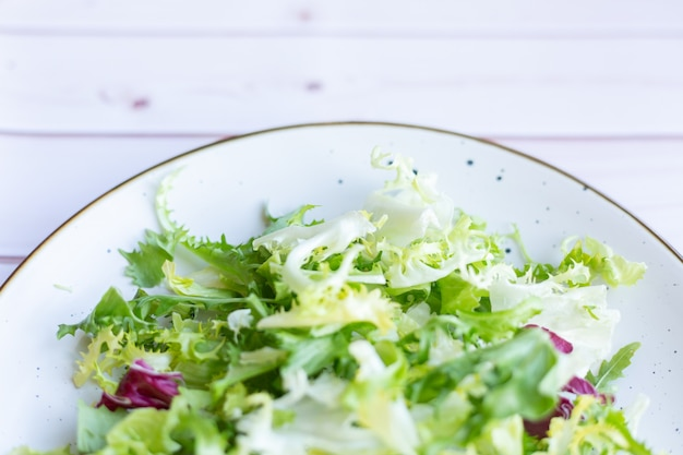 Weiße keramikplatte mit frischem salat auf holzoberfläche