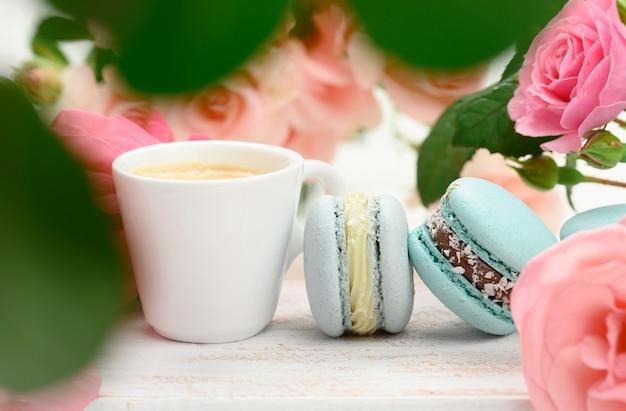 Weiße keramiktasse mit kaffee und macarons auf einem weißen tisch, hinter einem strauß rosa rosen, nahaufnahme