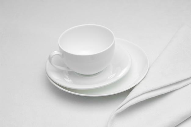 Weiße keramiktasse mit serviette auf weißem hintergrund