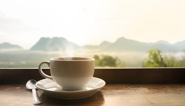 Weiße keramische kaffeetasse auf holztisch am morgen mit sonnenlicht über verschwommener gebirgslandschaft