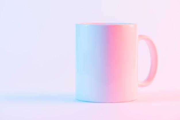Weiße keramische kaffeetasse gegen rosa hintergrund