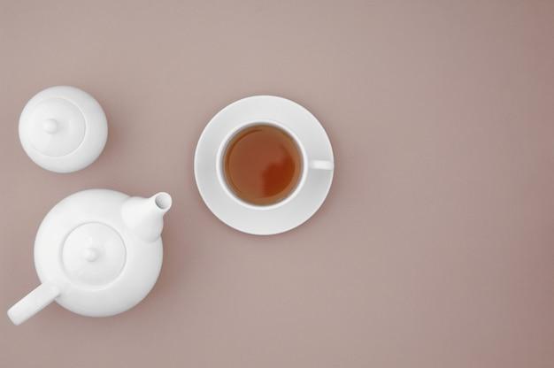 Weiße keramische teekanne mit tasse auf draufsicht des braunen hintergrundes