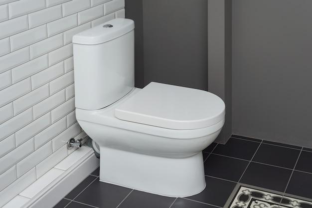 Weiße keramische toilettenschüssel in der badezimmerinnenraumnahaufnahme