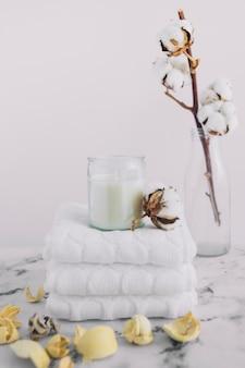 Weiße kerze im kerzenhalter über gestapelten weißen servietten nahe trockenen hülsen und baumwollzweig in der flasche