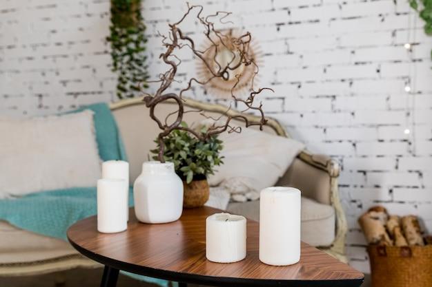 Weiße kerzen auf hölzernem couchtisch im gemütlichen wohnzimmerinnenraum. stilhaftes skandinavisches wohnzimmer. kerze und pflanze in vase auf kleinem holztisch vor skandinavisch gestaltetem sofa. boho nach hause