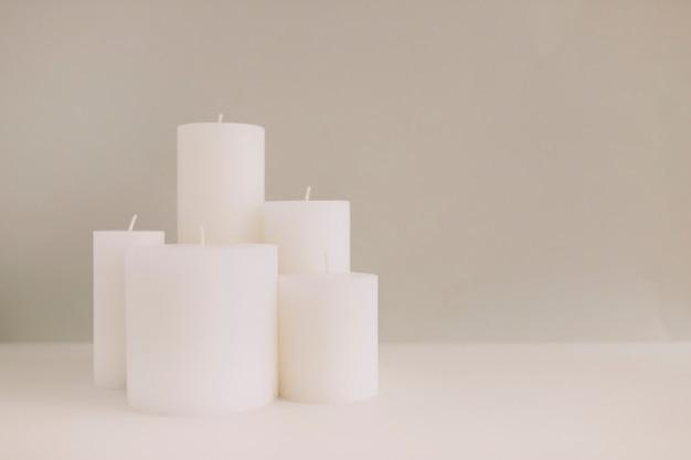 Weiße kerzen auf tischplatte gegen farbigen hintergrund
