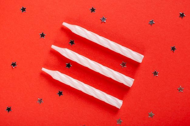 Weiße kerzenzusammensetzung auf roter hintergrund-, partei- und feierdekoration.