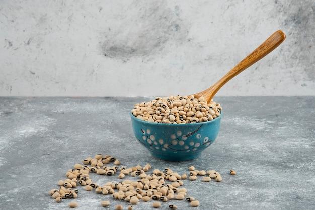 Weiße kidneybohnen in blauer schüssel mit löffel.