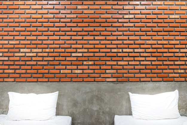 Weiße kissen in einem vintage- und loft-schlafzimmer mit braunem backsteinmauer-vintage-hintergrund