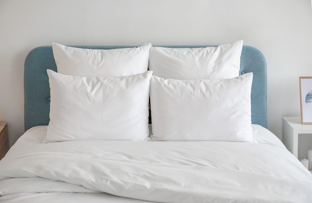 Weiße kissen und bettdecke auf dem blauen bett.