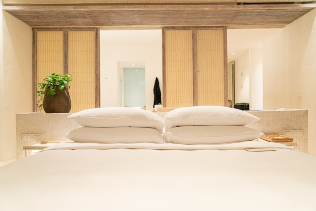 Weiße kissendekoration auf dem bett im schlafzimmer des luxushotelresorts