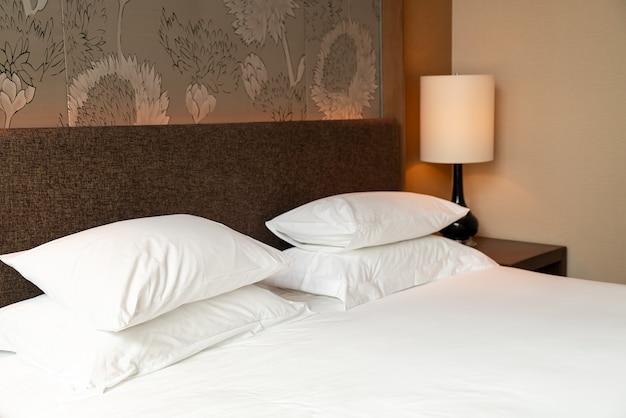 Weiße kissendekoration auf dem bett im schlafzimmer