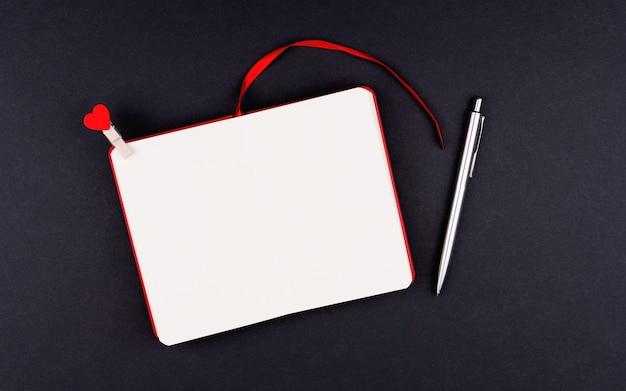 Weiße klare blattpostkarte am valentinstag, flache lage auf schwarzem hintergrund