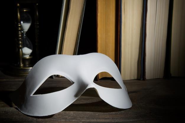 Weiße klassische karnevalsmaske auf buchhintergrund mit weinlesesanduhr auf holztisch
