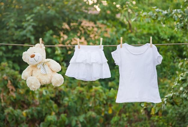 Weiße kleider trocknen im sommer an einem seil.